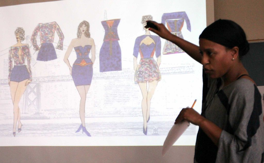 Apparel design and merchandising senior Laura Archid (right) showcases her two-minute elevator pitch in front of their Advanced Apparel Design Problems course in Burk Hall 410 on Wednesday, Feb. 10, 2016. The top five apparel designs that are chosen will be on display from Feb. 17 till March 2 in Burk Hall 334. (George Morin / Xpress)