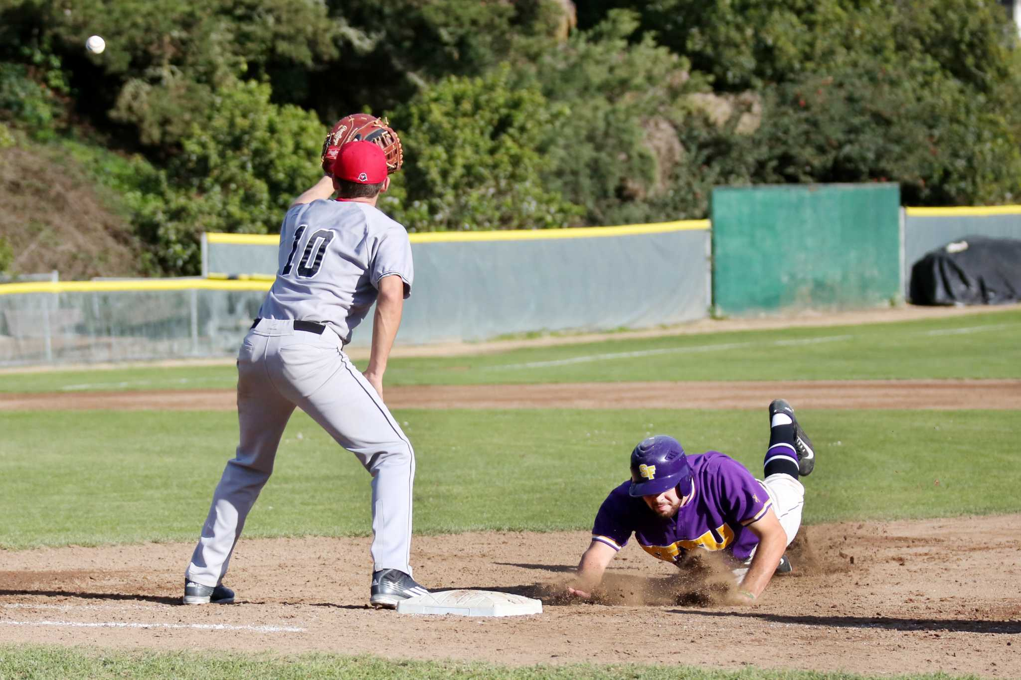 SF State Gator first baseman Ryan Burke (right) slides safely into first base as Holy Names University's first baseman Chris Gnos (left) waits for the ball during the Gators' second game of a doubleheader at Maloney Field at SF State on Saturday, Feb. 6, 2016. The Gators defeated the Hawks 4-3 in the second game of its doubleheader. (George Morin/Xpress)