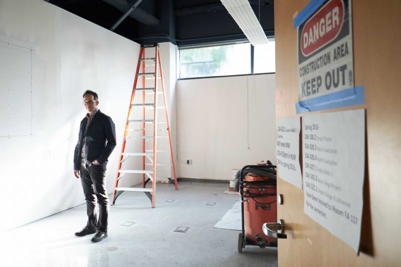 Director of the new Design Gallery, Joshua Singer stands in the doorway of the  exhibition space to be completed this Spring in the Fine Arts building. (Taylor Reyes / Xpress)