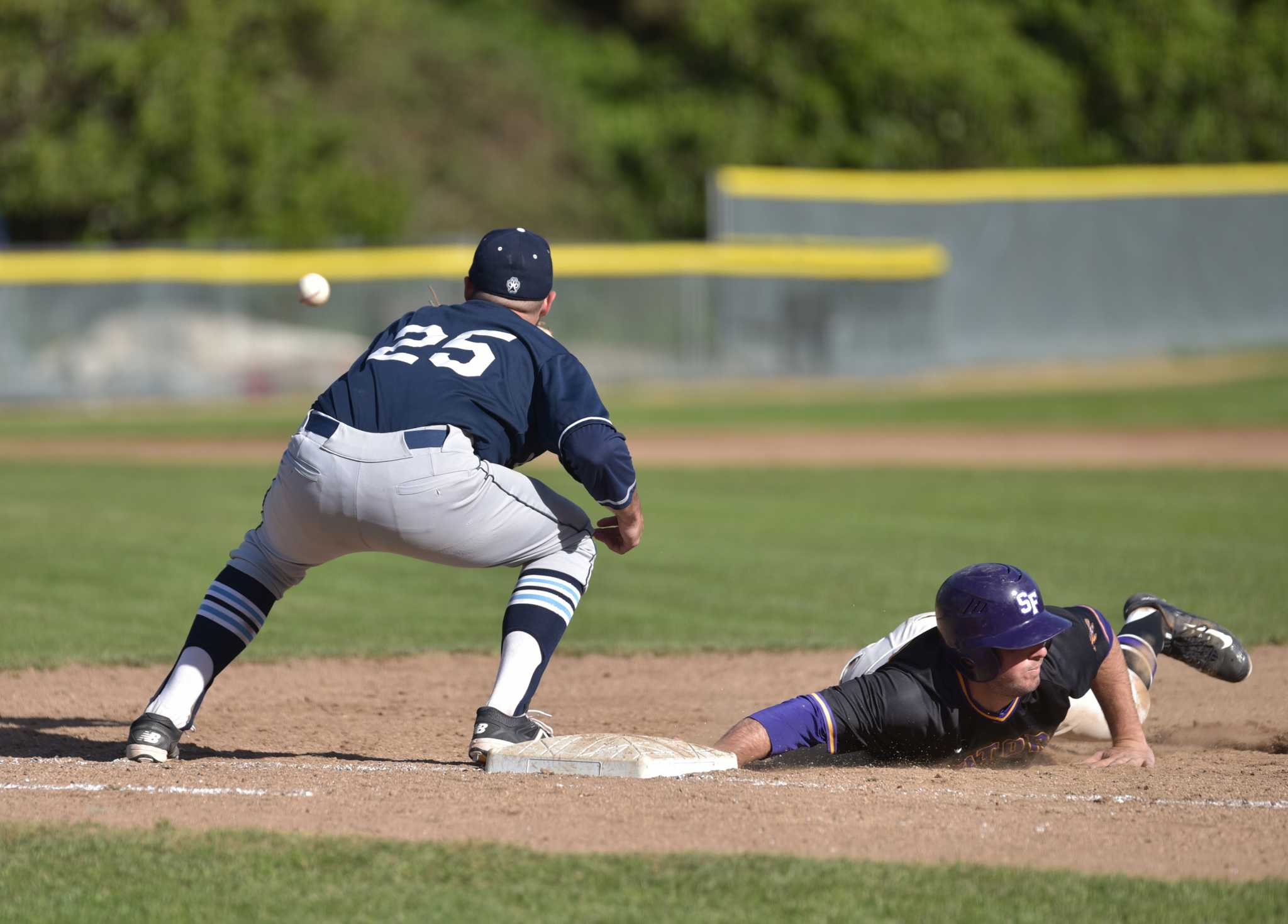 SF State Gators third baseman Connor Fraser (13) slides safely back to first base against Sonoma State Seawolves first baseman Tyler Glenn (25) in Gator's 6-1 win at Maloney Field in SF State Tuesday, Feb.23. (Qing Huang / Xpress)