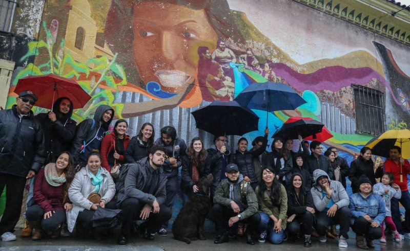 Volunteers for Clinica Martín-Baró and members of the community during the unveiling of the community mural that they painted on the side of La Palma Mexicatessen in the Mission District on Saturday March, 5, 2016.  (Aleah Fajardo / Xpress)