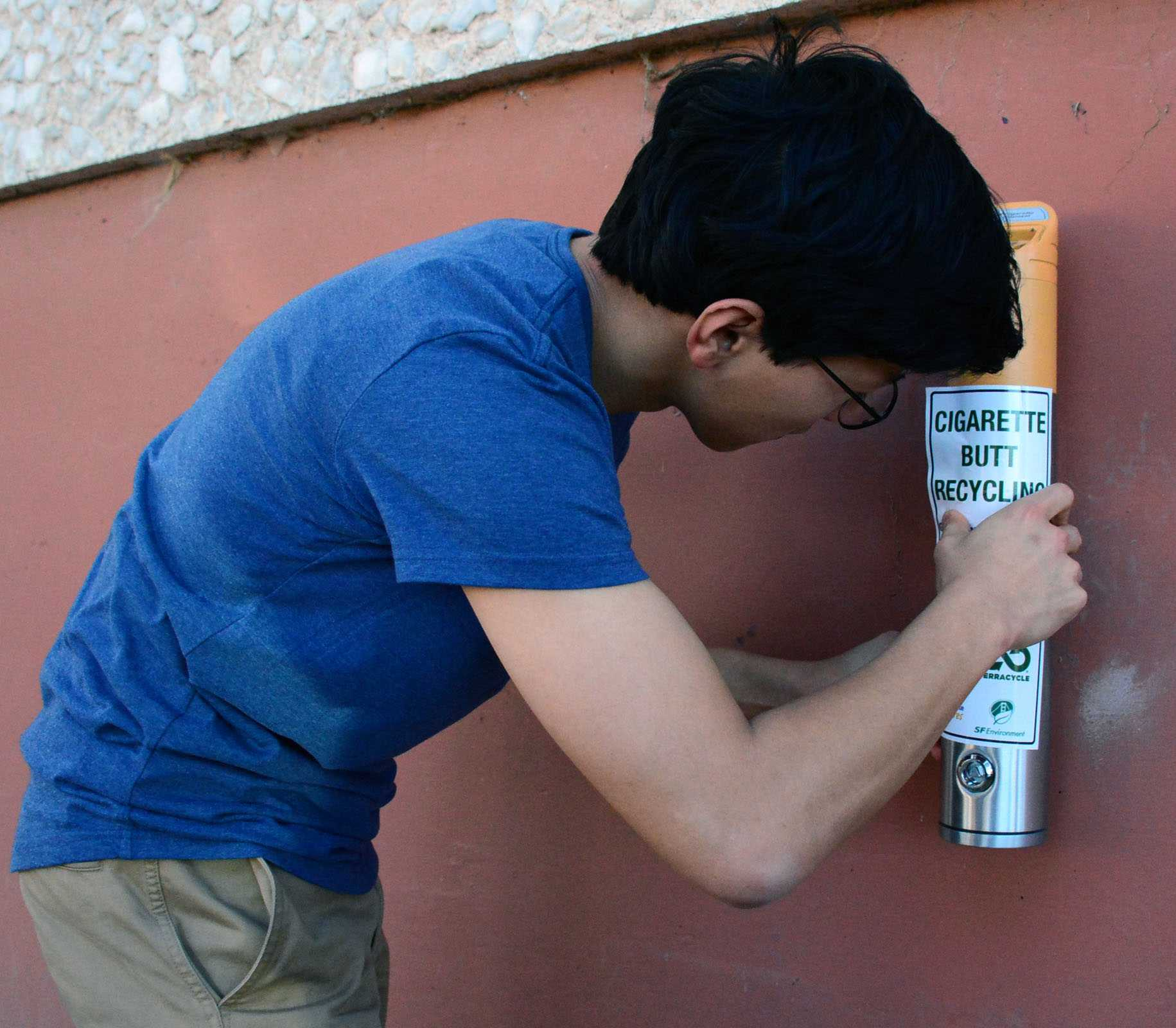 SF State student An Bui places the identifying sticker on the cigarette recycling bin located along Tapia Dive, Thursday, March 17, 2016. (Connor Hunt / Xpress)