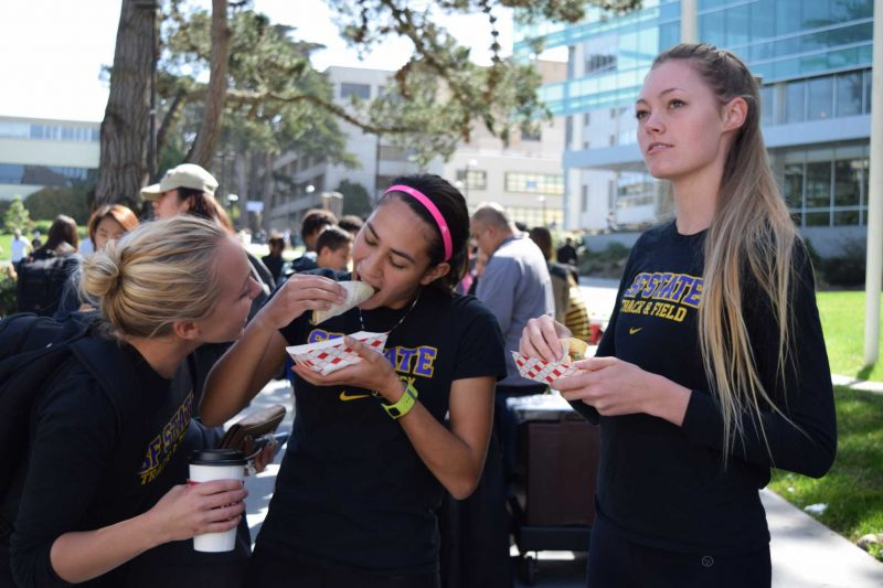 SF State Track and Field team members (left to right) Jacqueline Foley, Sophie Tait and Camille Hansen enjoy free Taqueria Girasol tacos on SF State's Founders Day, Tuesday, Mar. 15, 2016. (Gabriela Rodriguez / Xpress)