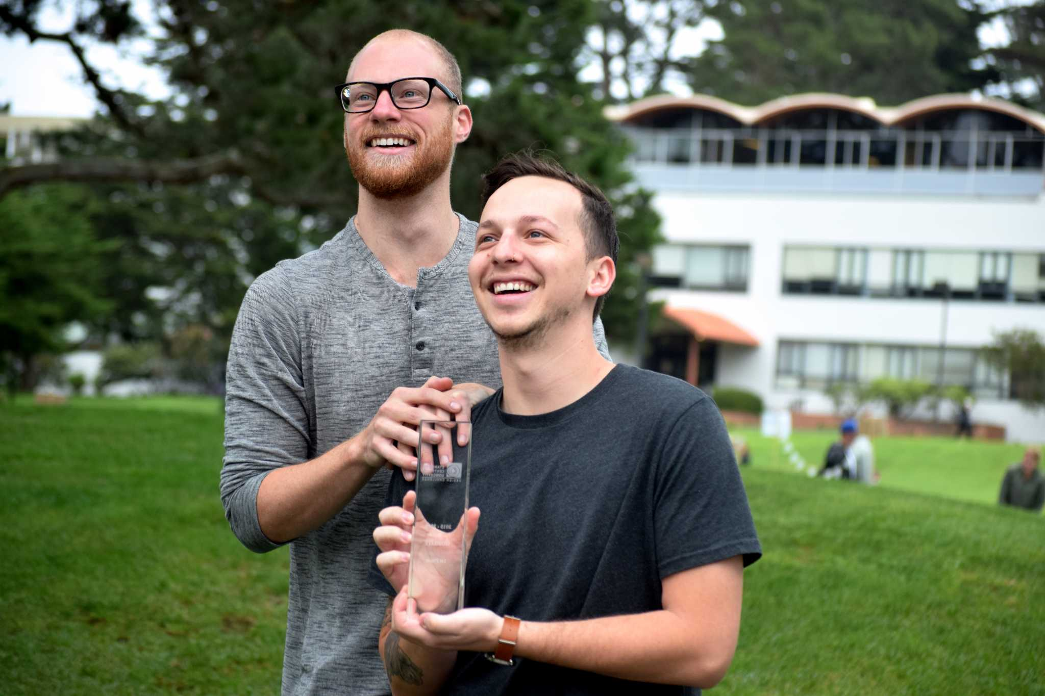 Eric Renard (left) and Brandon Lopez (right) pose for a portrait with their first place trophy from the Stanford Design Challenge. (Eric Chan / Xpress)