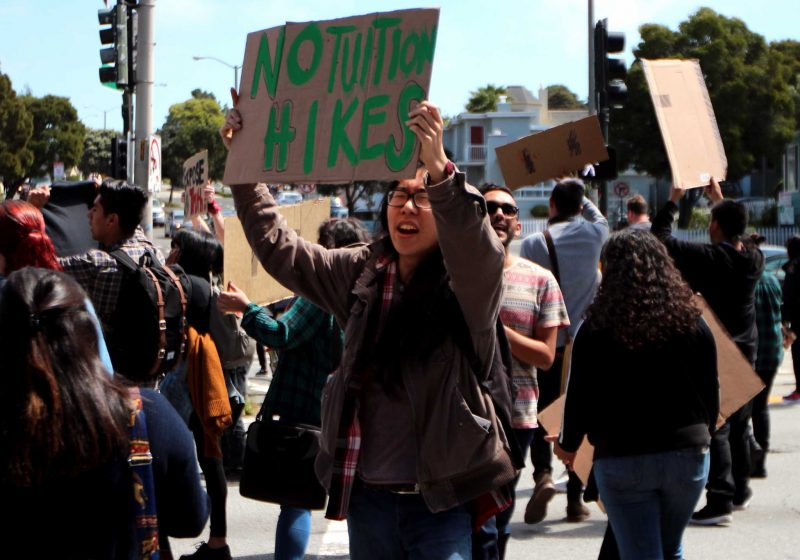 SF State Sociology student, Gary Pei, holds a sign as he crosses the street during a rally in which students came together to bring attention to a variety of issues happening on the SF State campus on 19th and Holloway in San Francisco, CA on Wednesday, April, 13, 2016. (Alex Kofman / Xpress)