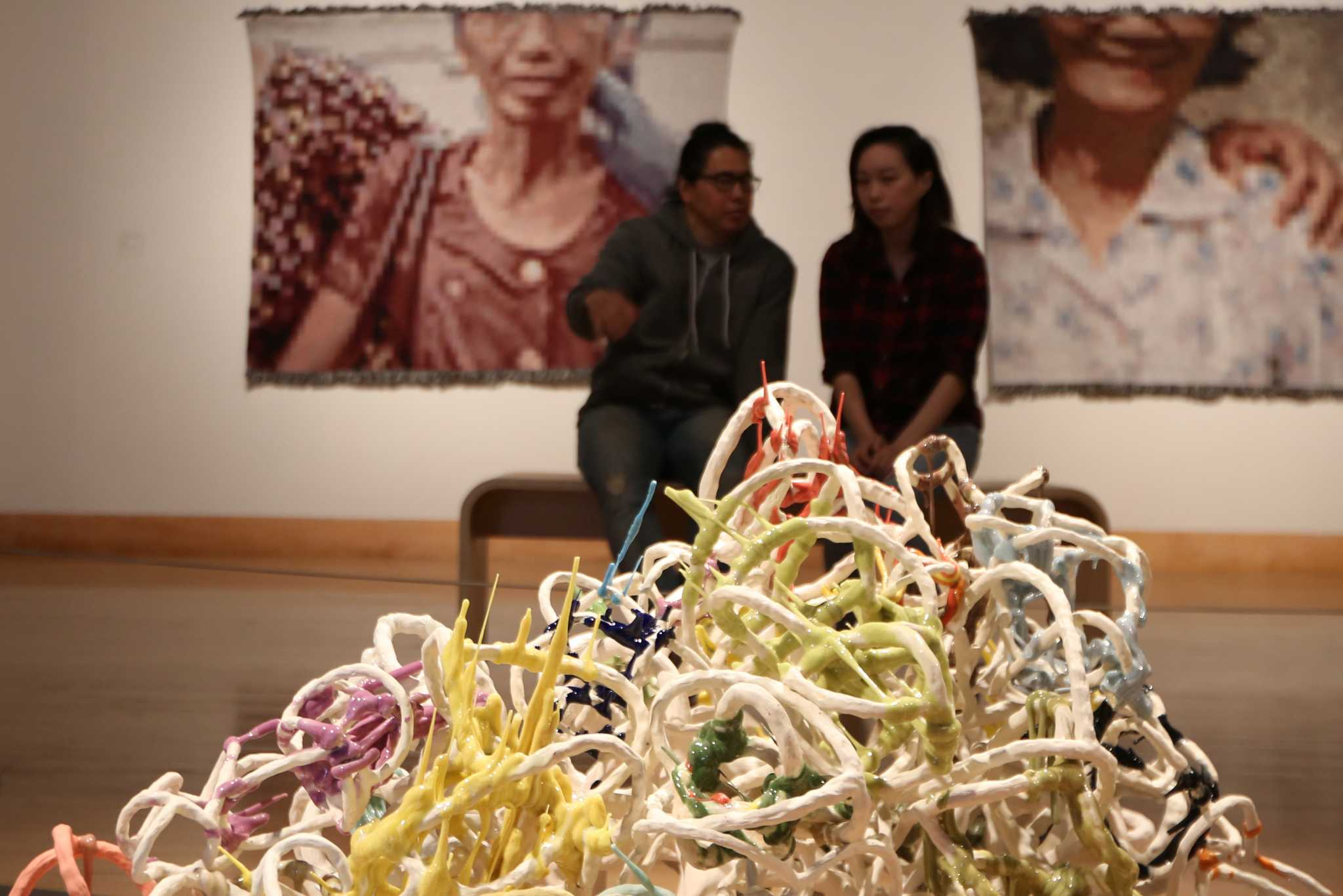 Attendees discuss a sculpture by Shannon Abac at the campus reception of the 2016 MFA Thesis Exhibition in the SF State Fine Arts Gallery on April 21, 2016. (Kelsey Lannin / Xpress