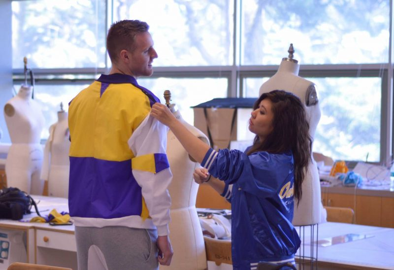 Apparel design student Becky Tu, 27, pins a sleeve on the upcycled bomber jacket she made with materials repurposed from the Bookstore, Monday, April 11, 2016. SF State basketball player Jon McMurry (left) will model the garment at the upcoming spring fashion show on April 28. (Emily Chavous / Xpress)