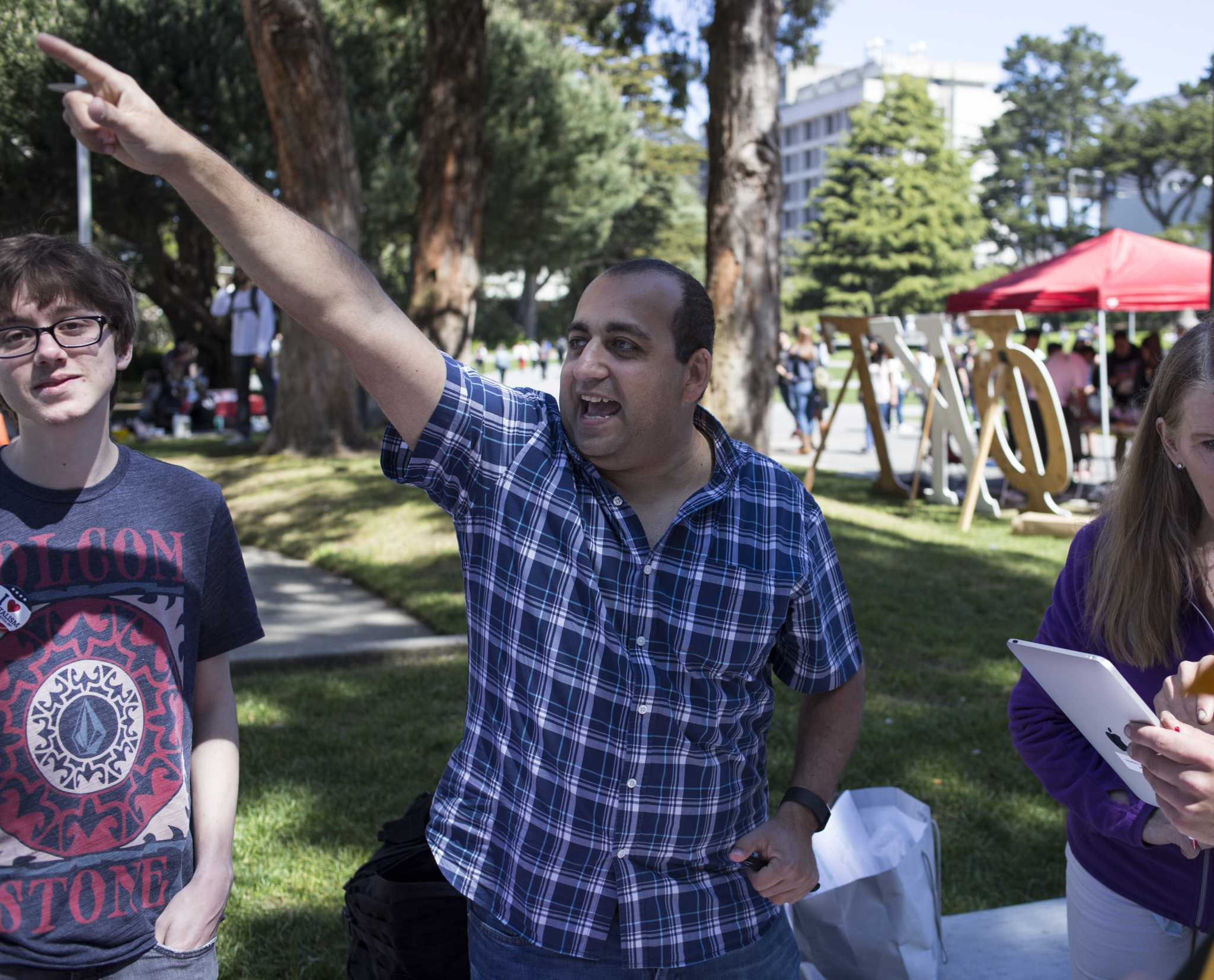 SF State student John Ayoub, the Young Republicans group leader, points toward the ethnic studies rally to draw attention to the fact that they were playing