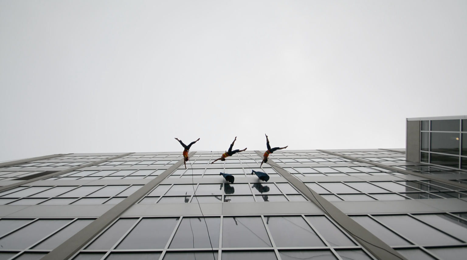 Aerial dancers suspended five stories above the ground during their performance at SF State on May 3, 2016. (Screen shot by: Ryan Zaragoza / Xpress)