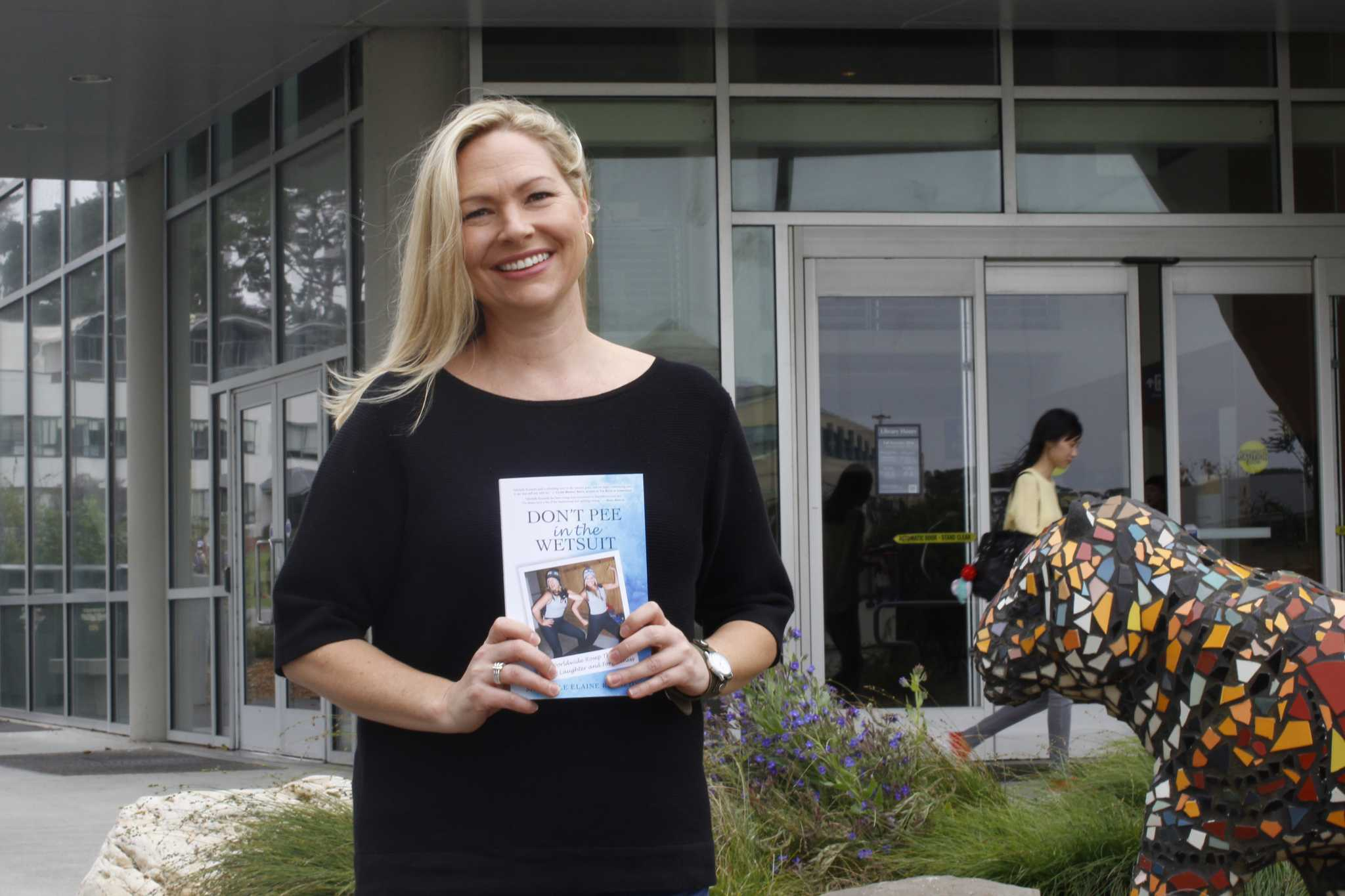 Author Michelle Kennedy poses with her book outside the library on Thursday, Sept. 8, 2016.