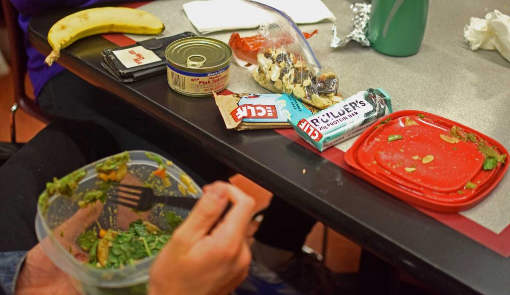 Drew Feldman, a member of the SF State's Men's Cross Country team, eats his lunch in the bottom floor of the Cesar Chavez Student Center on Tuesday, Sept. 13, 2016. His lunch consisted of a homemade salad, a banana, a can of salmon, multiple Cliff bars and a bag of mixed nuts and berries. (Eric Chan/Xpress)