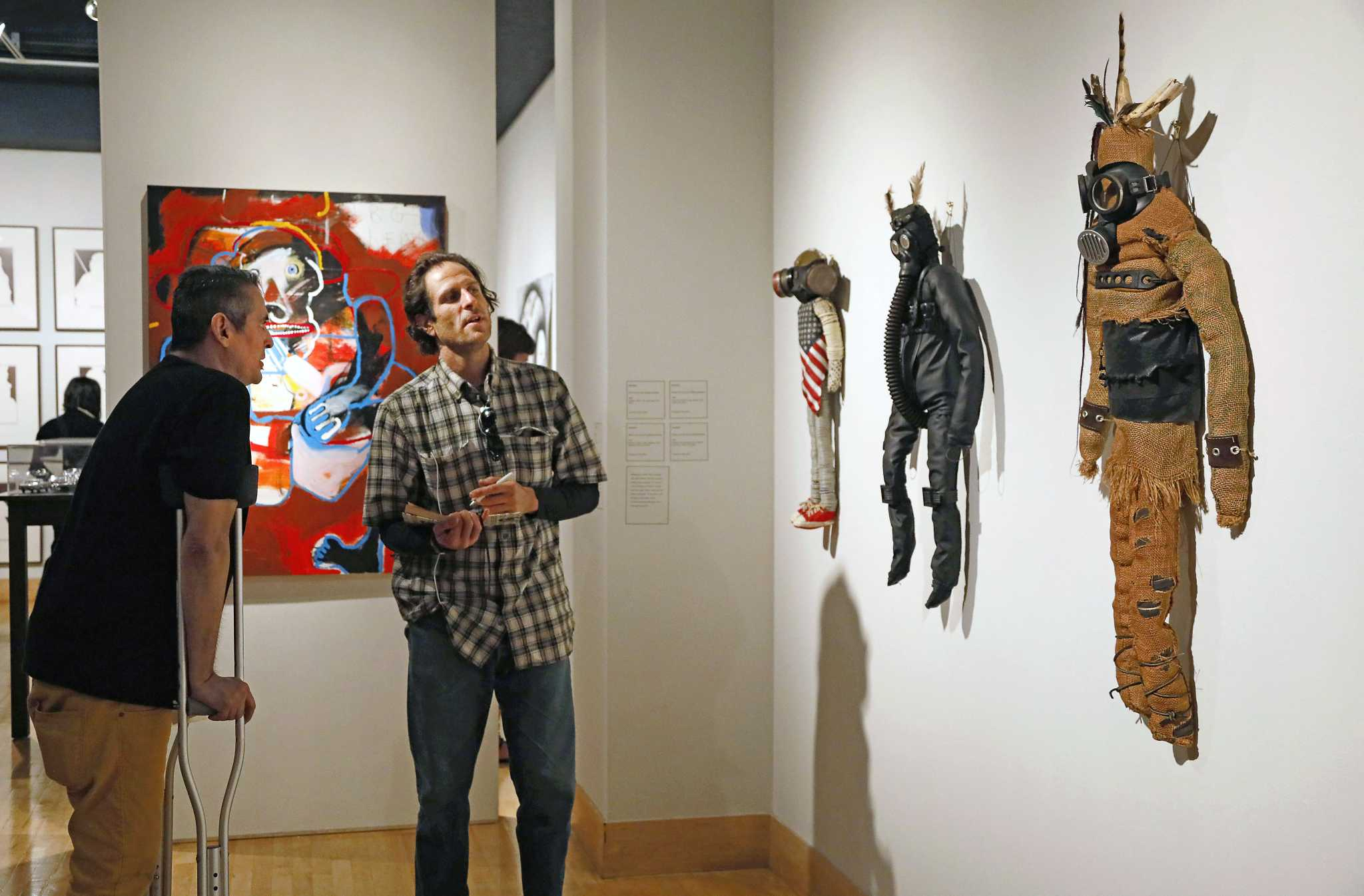 """Kevin """"Mooshka"""" Catawho talks to David Kertzman about his kachinas at the reception of the When I Remember, I See Red exhibit at the Fine Arts Gallery on Saturday, Sept. 17, 2016."""