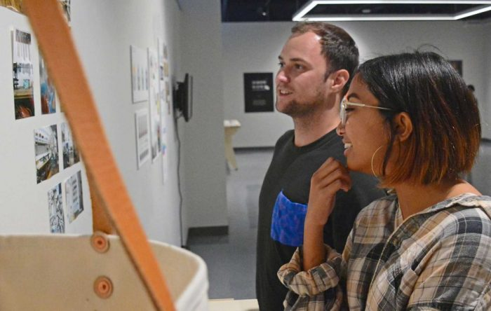 SF State School of Design seniors Gratas Sparnauskas (left) and Lorirae Francisco (right) look at some of the artwork in the Alumni Exhibition in the Design Gallery at SF State on Thursday Sept. 15, 2016.