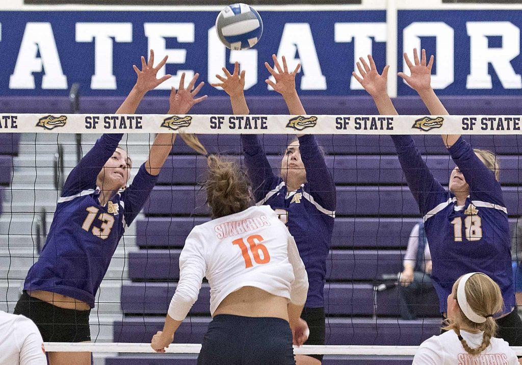 SF State Gator's sophomore outside hitter Willa Henderson (13), sophomore middle blocker Lauren Williams (2) and junior outside hitter Christine Johnson (18) block a spike by Sunbird freshman middle blocker Hailey Hilvers (16) during their loss to Fresno Pacific University at the Swamp on Friday, Sept. 9, 2016. The Sunbirds beat the Gators in three straight sets. (Kin Lee/Xpress)