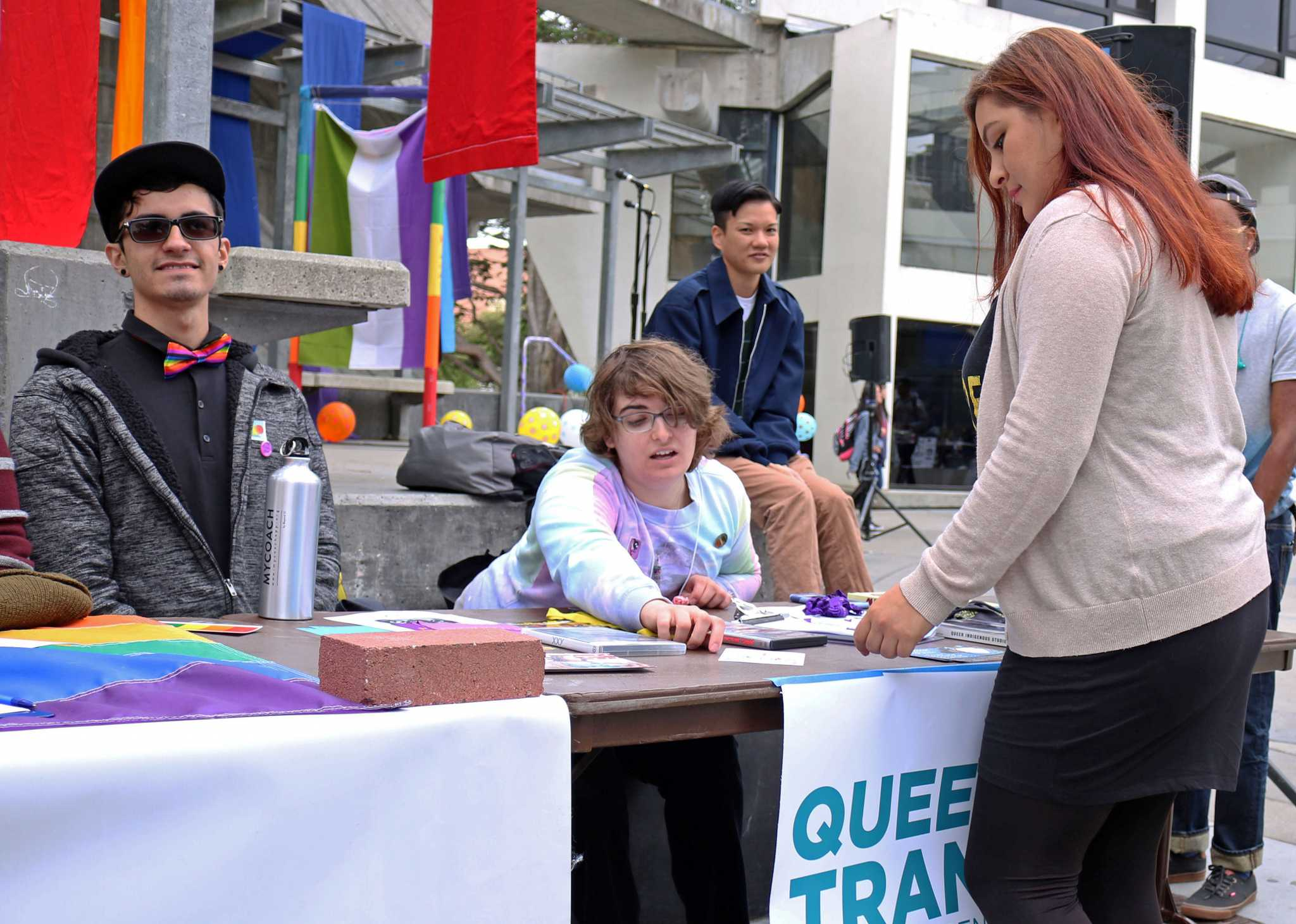 Queer Alliance and Trans Center members Alan Martinez (left) and Lauren Wolf (center) speak to a SF State student during the Coming Out Day event in Malcolm X Plaza on Monday, Oct. 10, 2016.
