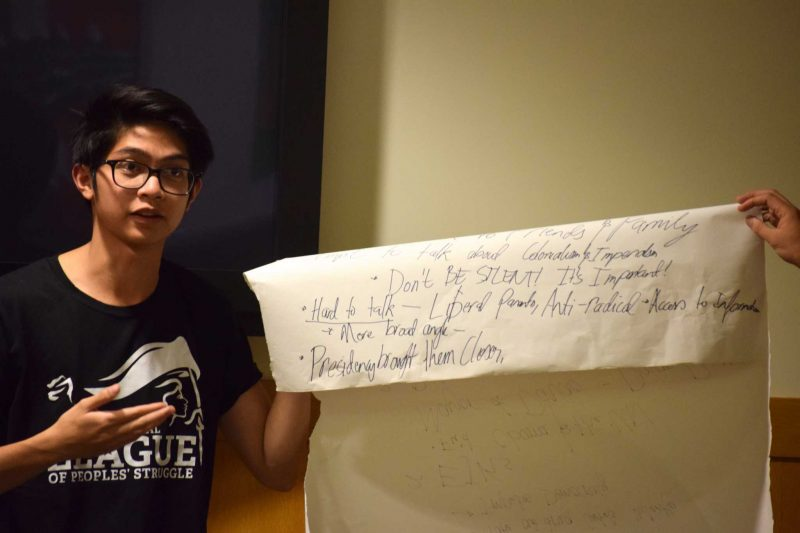 SF State student Raymond Jegillos holds up a poster with important topics put together by members of the League of Filipino Students during their peace talk forum in the Richard Oaks Multicultural Center in the Cesar Chavez Student Center on Thursday, October 20, 2016.