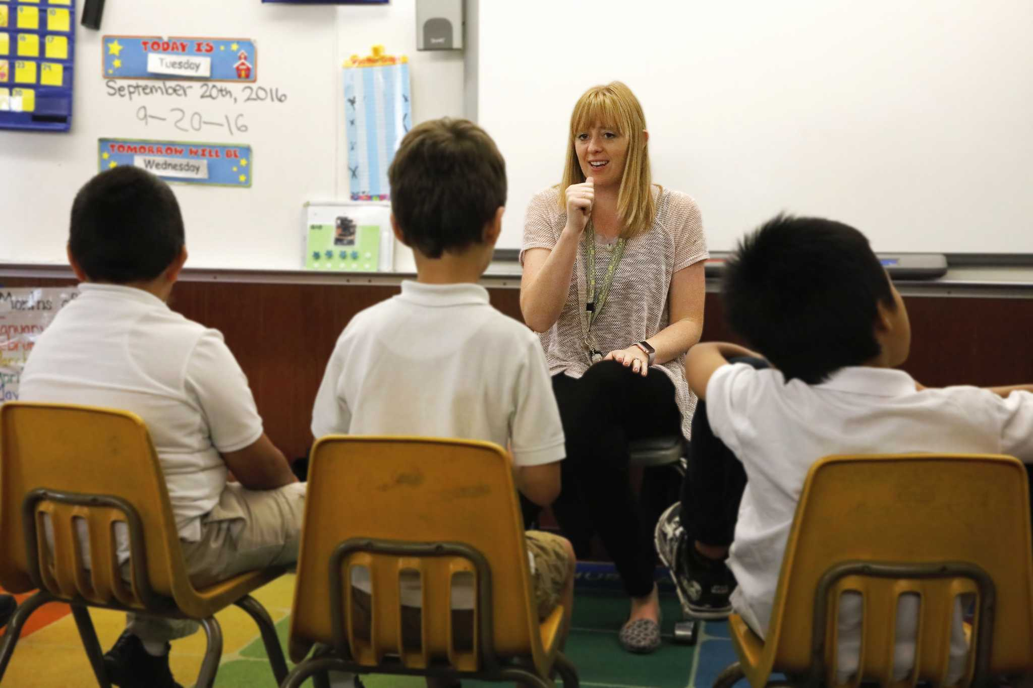 Kayla Kenton, a graduate of SF State's Moderate Severe Special Education program, uses sign language to communicate with children with autism during their morning sing-along at Junipero Serra Elementary School in Daly City, Calif. on Tuesday, Sept. 20, 2016.