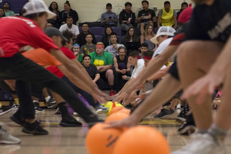 SF State students run to the center go the court to grab a dodgeball during the Campus Recreation Costume Dodgeball Tournament at the Swamp on Thursday, Oct. 20, 2016. The main goal of the event was to provide a chance for students to come together on a mostly commuter student campus.