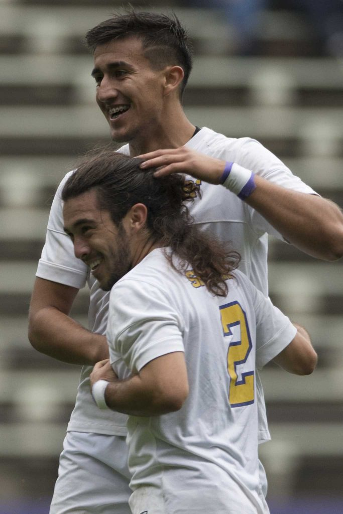 SF State Gators' junior midfielder Francisco Saucedo (19) and junior midfielder KJ Ahlo (2) celebrate after Saucedo scored his second goal during their 6-1 win over Cal State East Bay at Cox Stadium on Thursday Oct. 27, 2016. Saucedo scored his first two goals of the season.