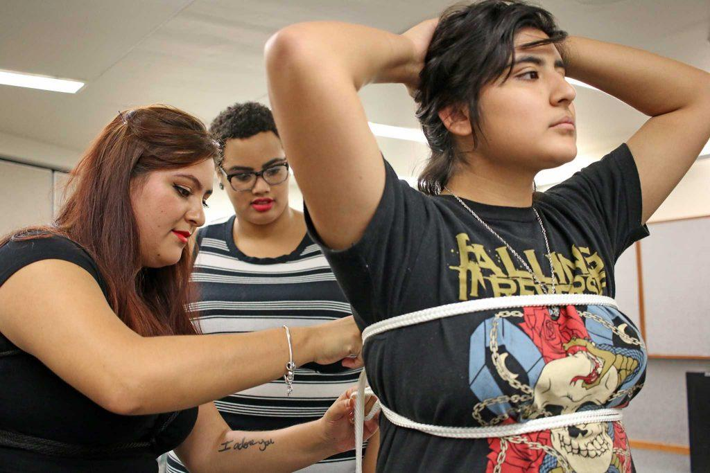 SF State's Education and Referral Organization for Sexuality director Reyna Aguilar (left) shows SF State computer science major Maya Chatman (center) how to perform a double limb rope bondage on pre-child adolescent development major Felicia Macedo (right) during the Playing by the Ropes: Kink & Bondage 101 event in the Rosa Parks Conference Room on Wednesday, Oct. 26, 2016. (George Morin/Xpress)