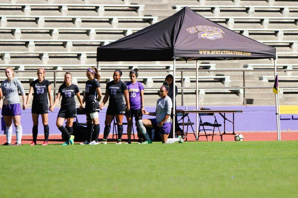 SF State Gators goalkeeper  Arianna Wesley (bottom right) kneels during the playing of the national anthem before a game against Cal State San Marcos at Cox Stadium on Sunday, Oct. 9.