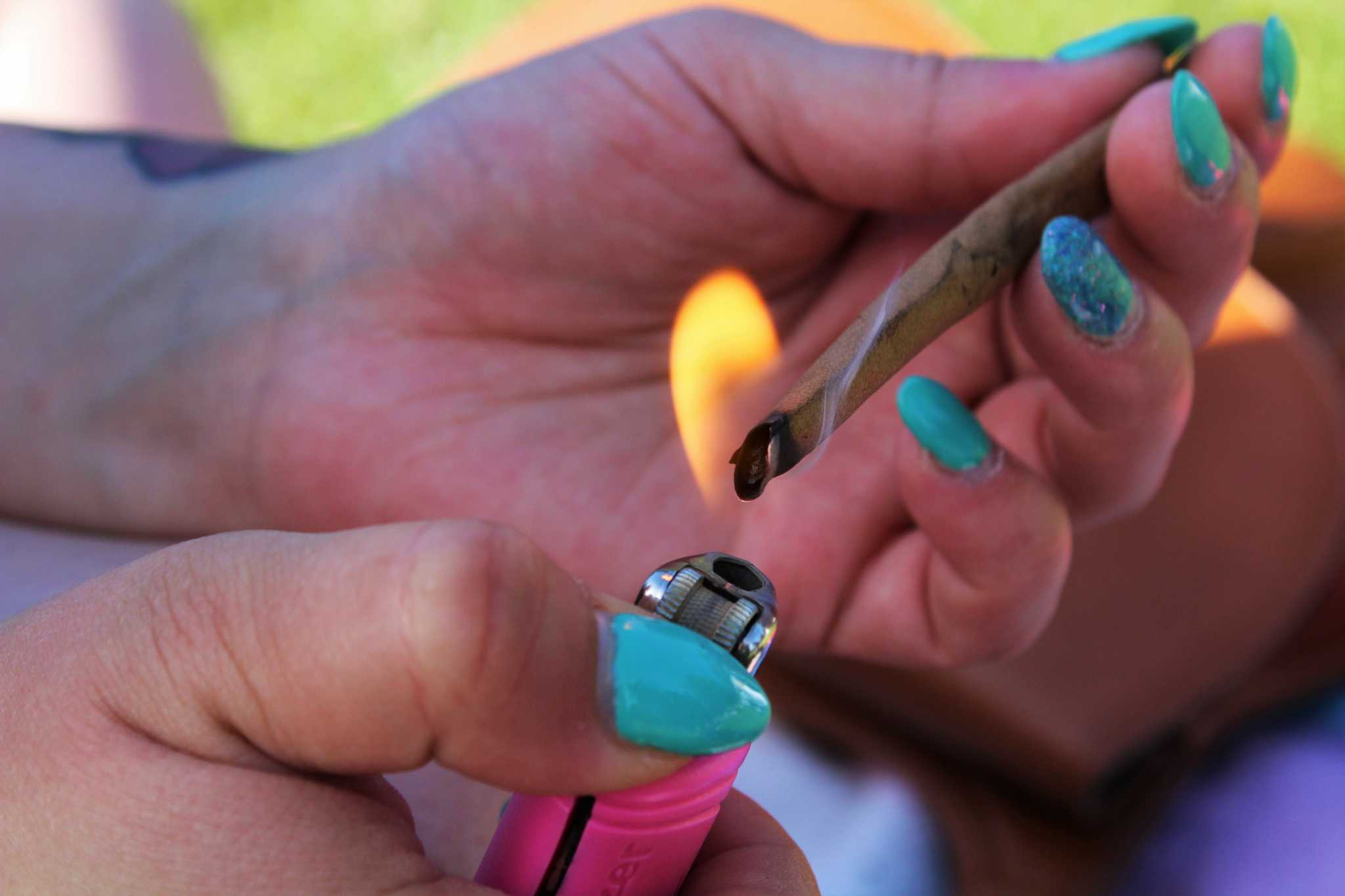 Amanda Clanton, 24, sparks up a marijuana cigarette in Golden Gate Park on April 4, 2015 in San Francisco, Calif. Photo by Alina Castillo.