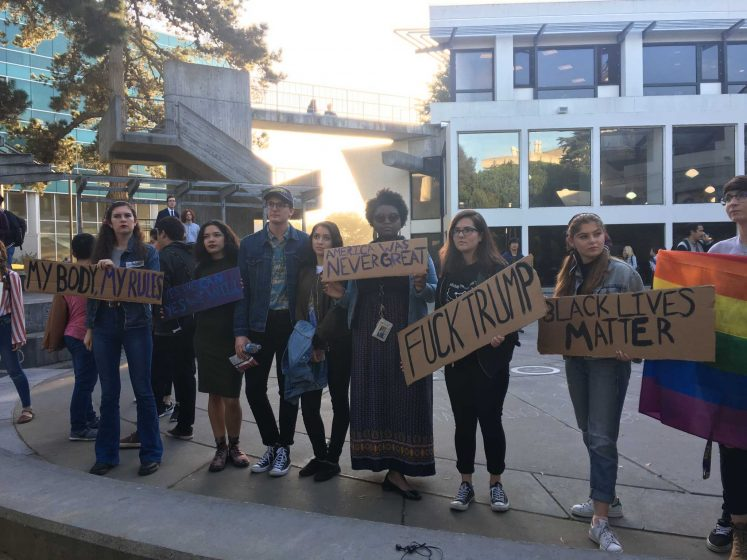Students pose for a picture in Malcolm X Plaza at SF State holding signs in protest of President Elect Donald Trump winning the presidency on Nov. 9, 2016 (Breanna Reeves/ Xpress).