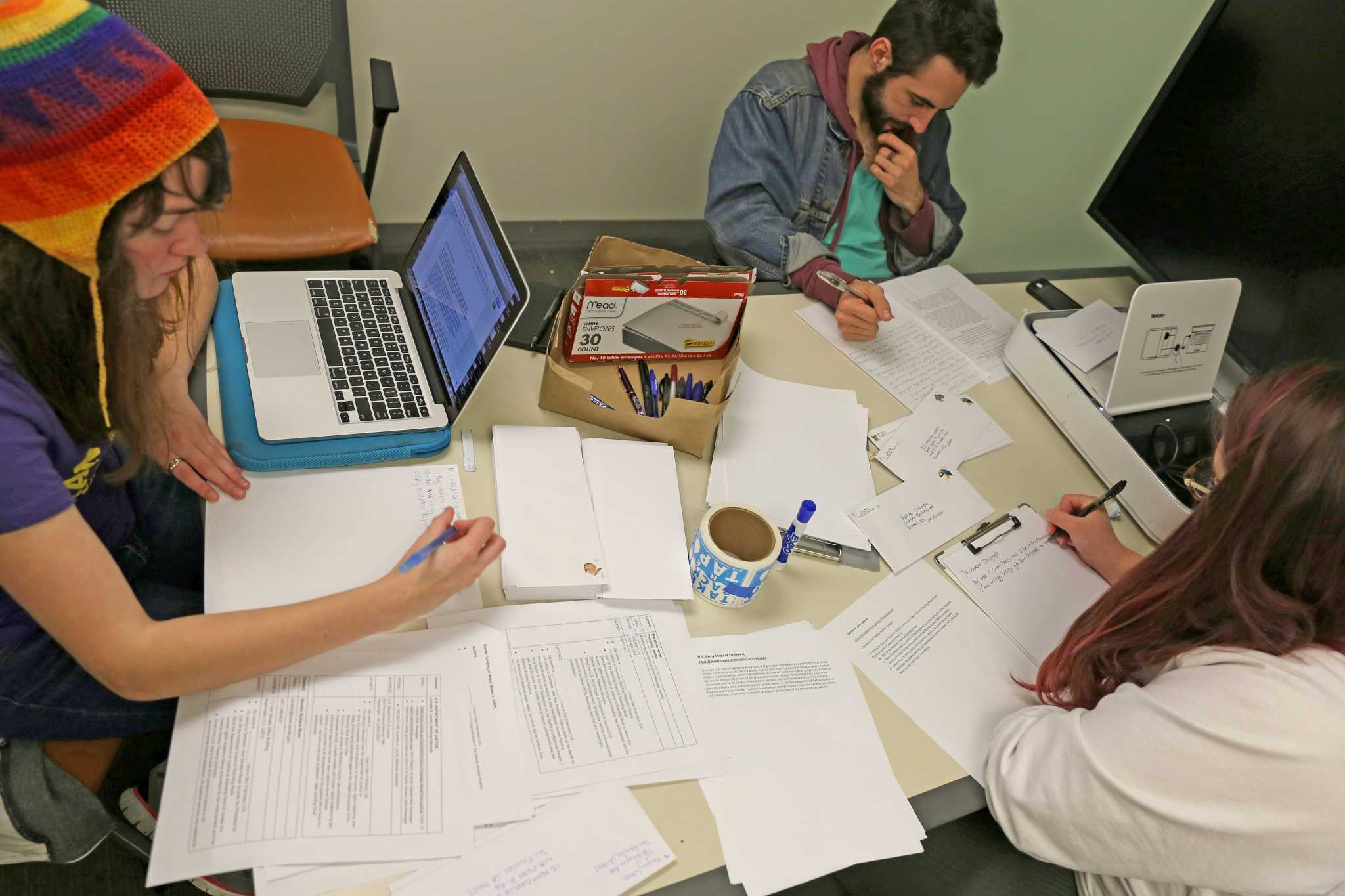 Environmental studies majors, Liana Derus (white), Tom Evans and business major Hayley Woods write letters to members of congress regarding the Dakota Access Pipeline in the J.P. Leonard Library on Monday, Nov. 28, 2016. Liana Derus, member of SF State's ECO Club organized the event.