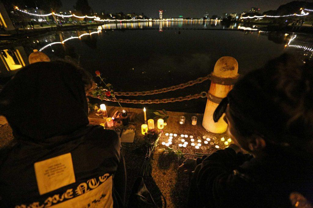 Two people light candles next to Lake Merritt during a candlelight vigil for the victims of the Ghost Ship artist warehouse fire, in Oakland, Calif. on Monday, Dec. 5, 2016. (George Morin/Xpress)