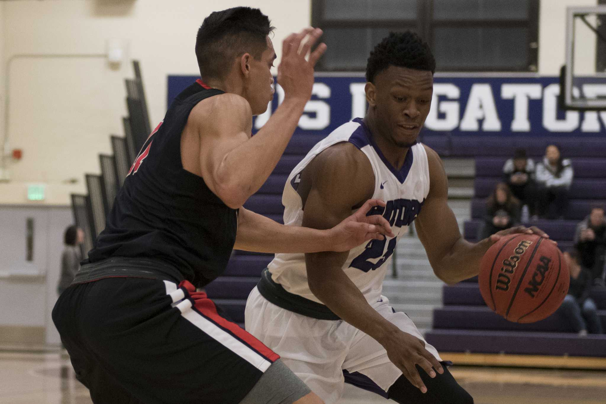 SF State Gators' sophomore guard Chiefy Ugbaja (23) drives to the basket against Pioneers' senior forward Micah Dunhour (11) during the Gators' 80-65 win over Cal State East Bay at the Swamp on Saturday, Dec. 3, 2016.