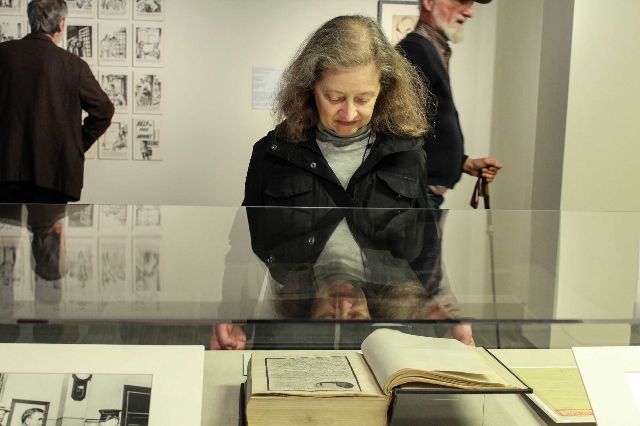 San Francisco resident Lisa Dunseth looks at a book during the exhibit of the San Francisco Preparedness Day Bombing in 1916 in the J. Paul Leonard Library on Tuesday, Nov. 29, 2016. Photograph by: Kayleen Fonte