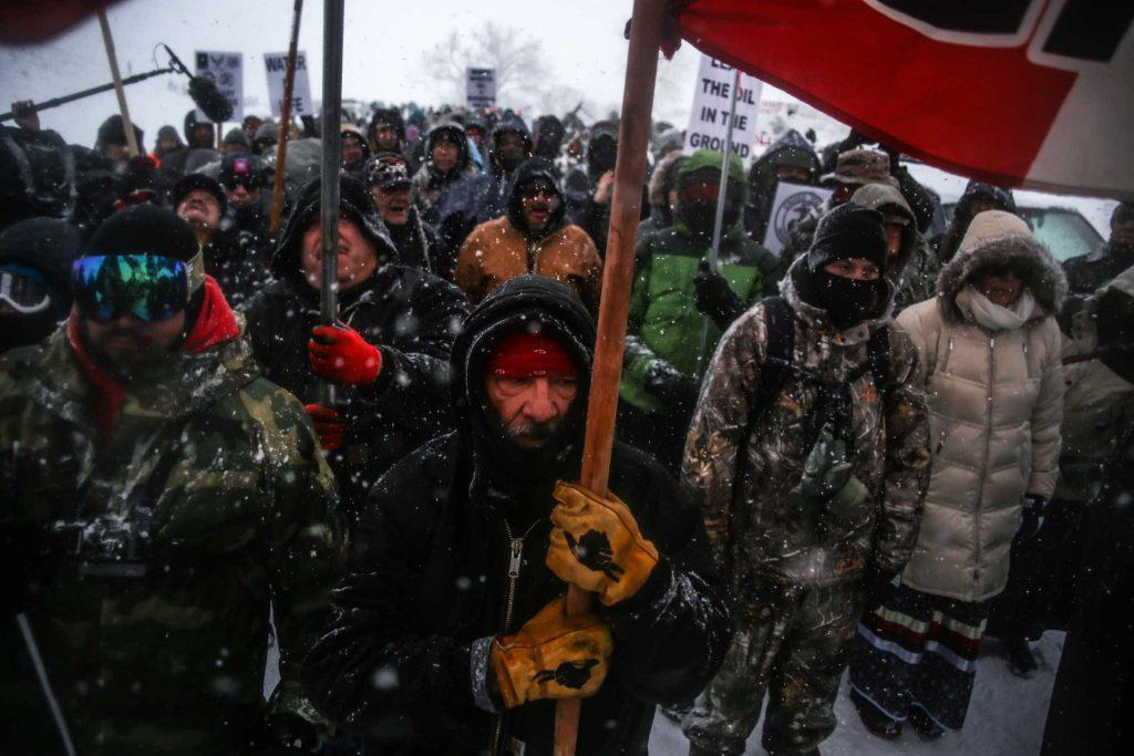 Water protectors march with support from US military veterans toward barricades on Highway 1806 blocking road access to the construction site of the Dakota Access Pipeline during a blizzard in freezing temperatures at the Standing Rock Indian Reservation in Cannon Ball, North Dakota on December 5, 2016. (Photo: Joel Angel Juarez)