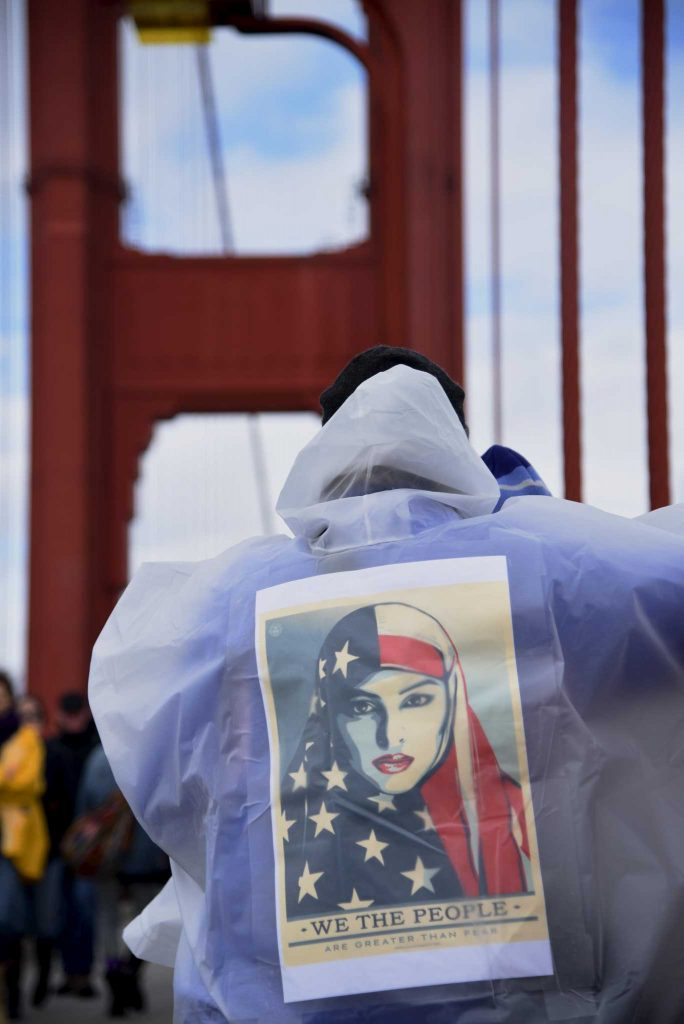 Liza Loeffler wears Shepard Fairey's inauguration poster on her back at the Golden Gate Bridge in San Francisco, Calif., on Friday, January 20, 2017.