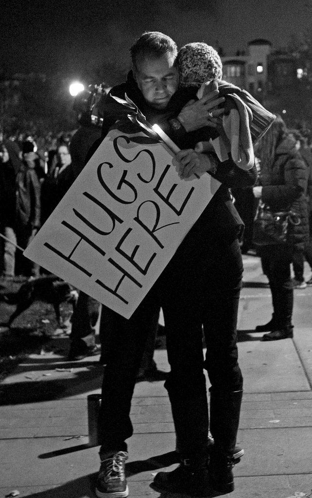 A+person+holding+a+%22Hugs+Here%22+sign+hugs+another+person+during+a+candlelight+vigil+for+the+victims+of+the+Ghost+Ship+artist+warehouse+fire%2C+at+Lake+Merritt+in+Oakland%2C+Calif.+on+Monday%2C+Dec.+5%2C+2016+%28George+Morin%2F+Xpress%29.