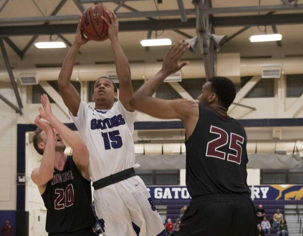 SF State Gators guard Israel Hakim (15) drives through the defense of Chico State Wildcats guard Nate Ambrosini (20) and freshmen center Justin Briggs (25) and goes for the basket during the Gators' 65-51 win over the Wildcat at the Swamp on Saturday, Feb. 4, 2017 (Lee Kin/ Xpress).
