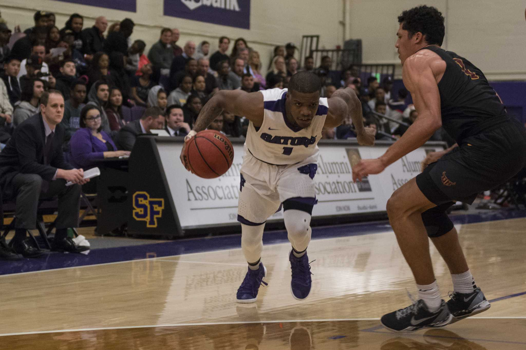 SF State Gators' junior guard Warren Jackson  drives in while guarded by CAL State Dominguez Hills Toros' junior guard Khalil Bedart-Ghani during the Gators' 78-68 win over the Toros at Swamp in San Francisco on Friday, Feb. 17, 2017. (Lee Kin/ Xpress)