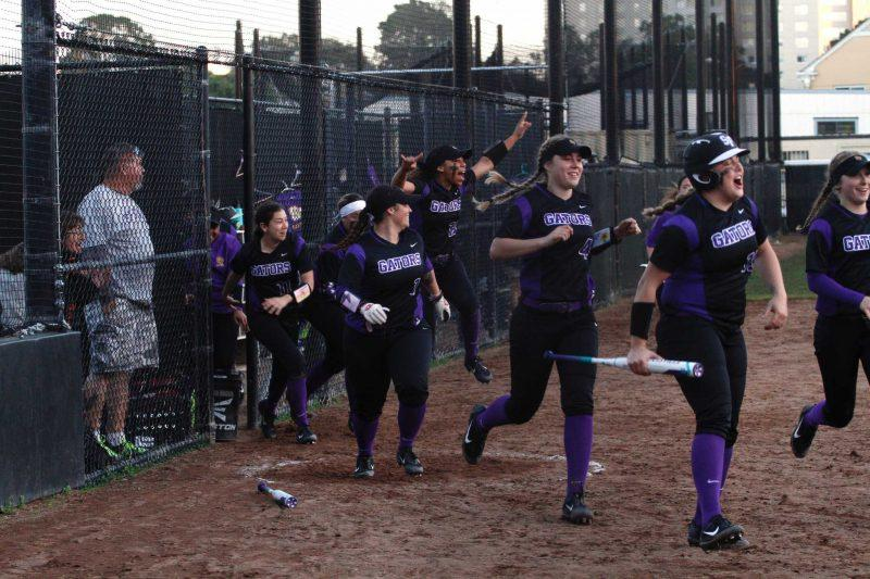Teammates run out of the dugout to celebrate SF State Gators' Celeste Adriano's (12) home run, which broke the 3-3 tie against the Cal State East Bay Pioneers in the 7th inning brining in two runs on Saturday, February 11, 2017 in San Francisco, Calif., at SF State. The Gators went on to win 5-3 (Mason Rockfellow/Xpress).