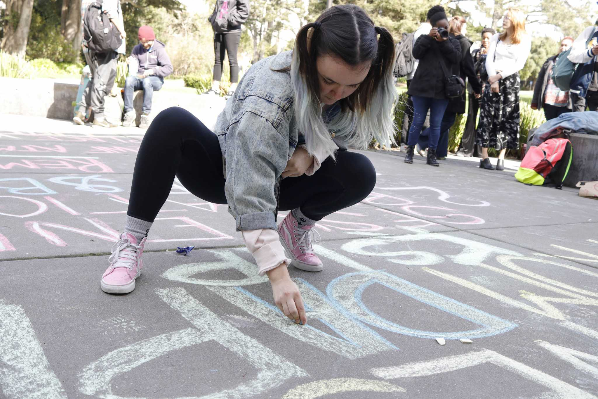 Julia Grace, 22, women and gender studies major, writes in chalk in front of the Wells Fargo and Bank of America ATM machines during the protest against the DAPL and KPL funding from the two banks. (Mason Rockfellow/Xpress)