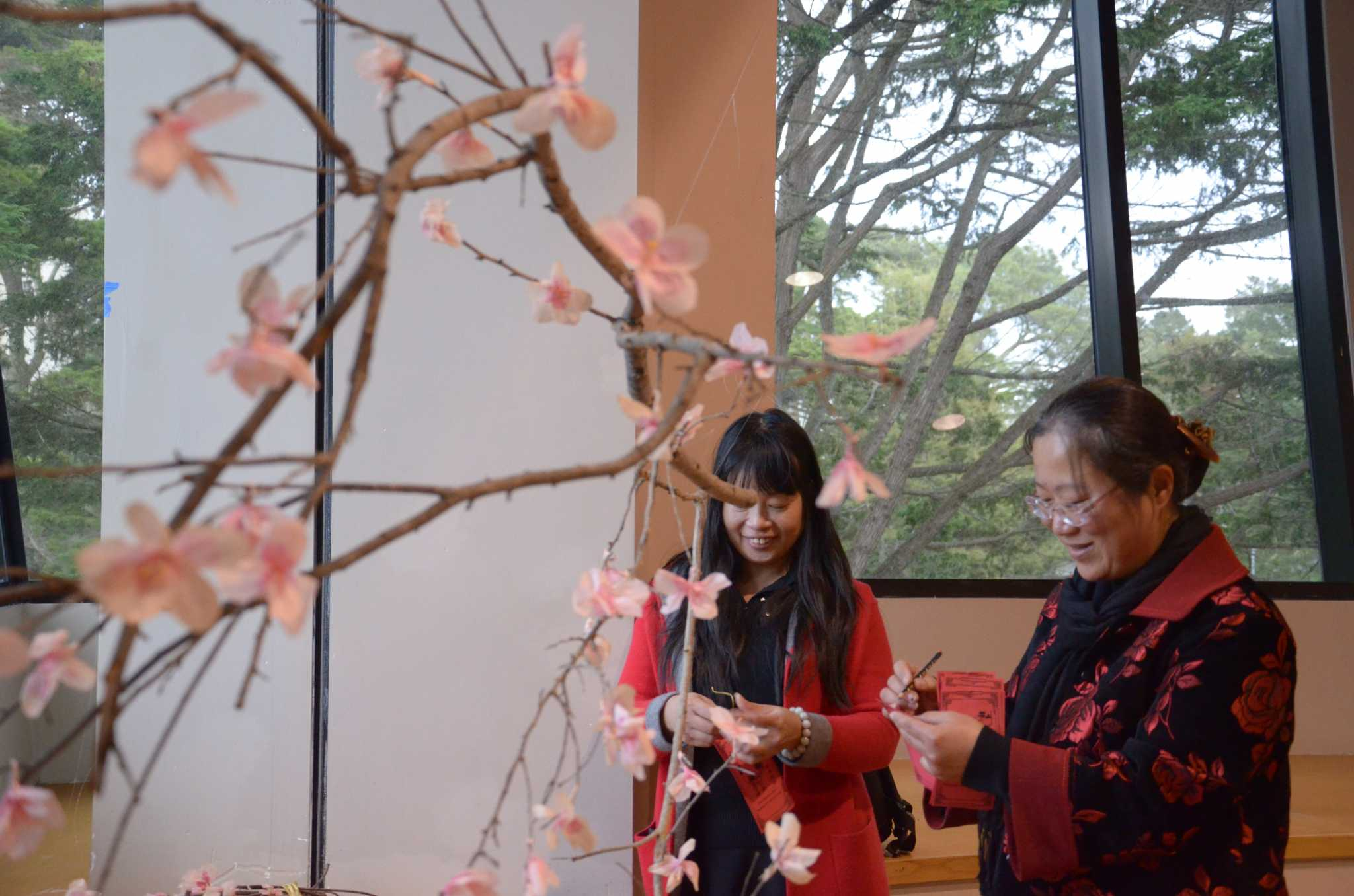 Chinese language students Yafang He, and Liyao Zhu hang their wishes on a wishing tree at the Chinese New Year celebration held on Feb. 3, 2017 at Jack Adams Hall. (Christianna Fjelstad/Xpress)