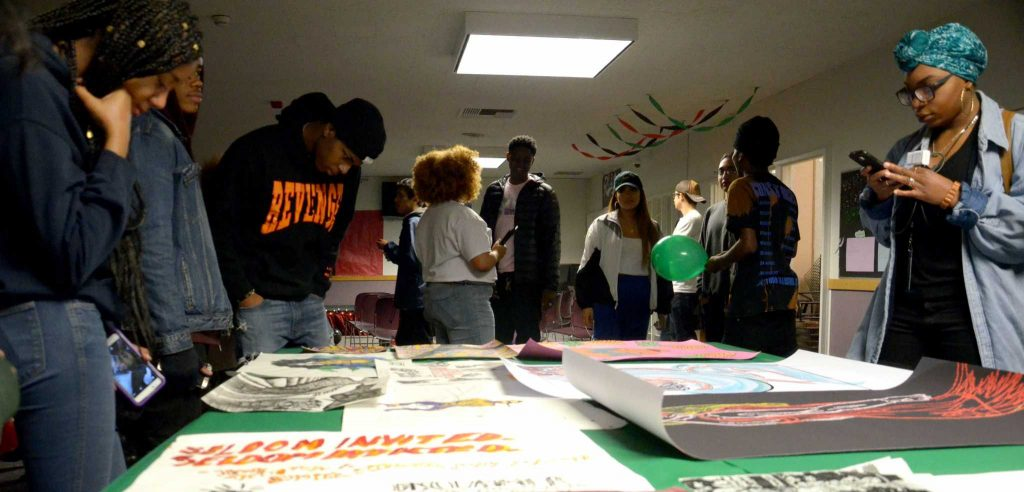 Students look at artwork displayed at the B.R.U.H open mic event at SF State's Mary Park Lounge on Friday, Februray 24, 2017 (Christianna Fjelstad).