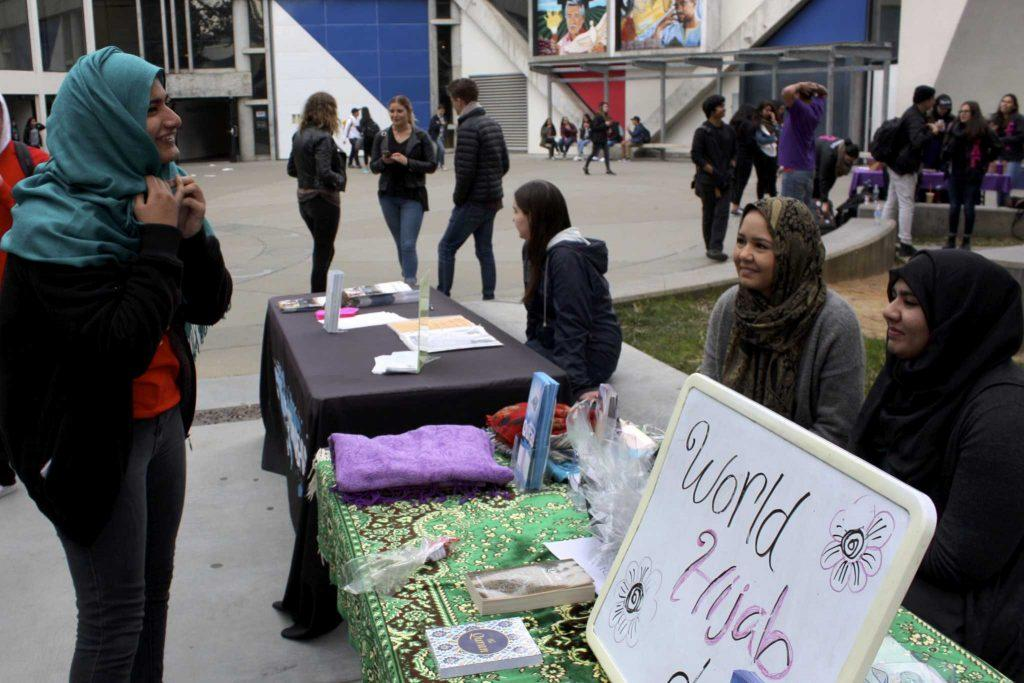 A student tries on hijabs in the quad for World Hijab Day on Feb. 1, hosted by the Muslim Women Student Association. (Olivia Mendez / Xpress)