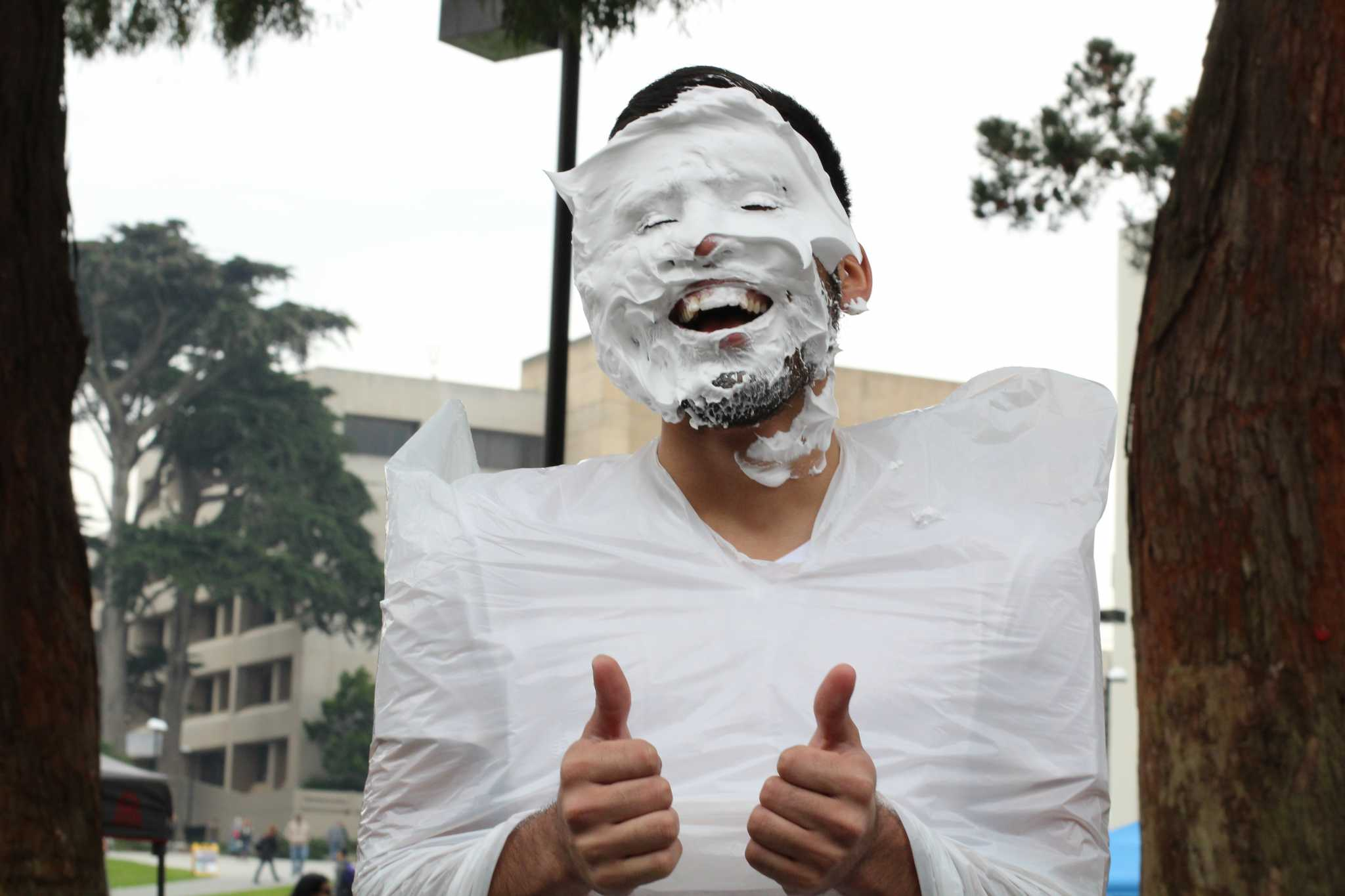 Arturo Dominguez gives two thumbs up after being pied to raise awareness for the Hermanos Unidos de SFSU organization in front of the Cesar Chavez building on February 1, 2017 in San Francisco, Calif. (Alina Castillo/Xpress)