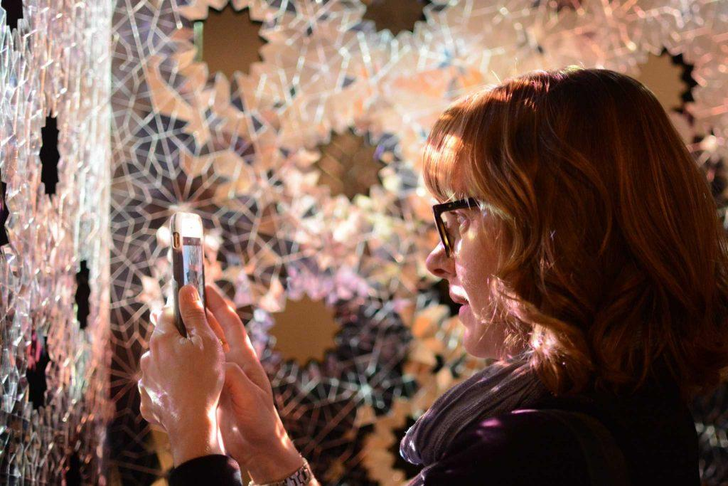 Michelle Jones, 39, an art history major at SF State from San Carlos, Calif. uses her phone to photograph Sanaz Mazinani's reflective, visual and sound-based art piece Threshold during the Mashrabiya - the art of looking back - art gallery opening reception in the Fine Arts building at SF State on Saturday, February 18, 2017. (Aaron Levy-Wolins / Xpress)