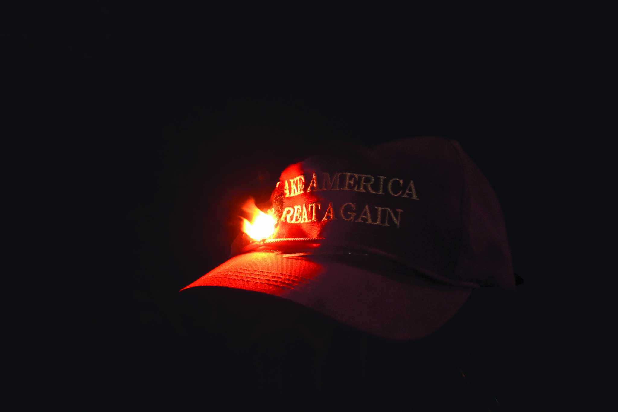 A Trump Supporter's hat is set on fire at a riot protesting controversial speaker Milo Yiannopoulous, who was scheduled to speak Feb. 1, 2017. The event was canceled due to violent riots (Tate Drunker/Xpress).
