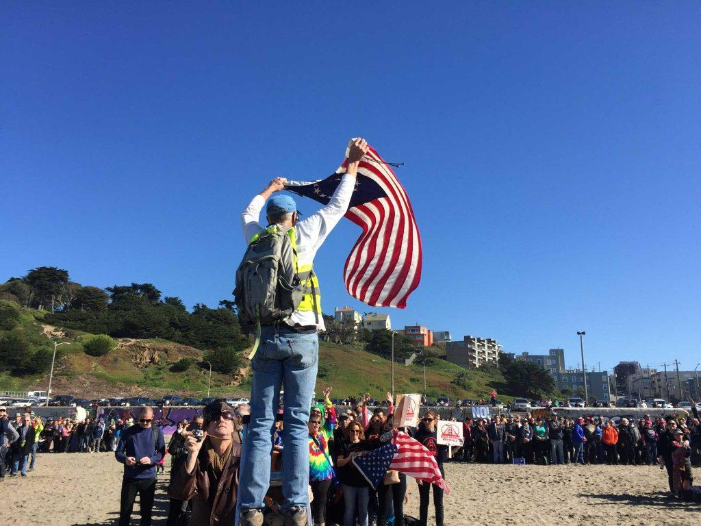 Brad Newsham waves a 13-star flag above his head as he directs thousands of volunteers to spell out the word