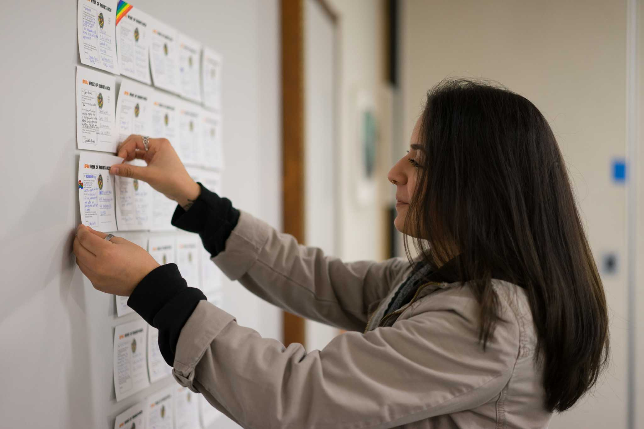 Gabriela Ceeros, a junior majoring in Latina studies, adds her letter to the wall for the Week of Resistance where students can find contact information for their district representatives and state senators to send letters addressing their concerns about the immigration ban by Donald Trump, in the Cesar Chavez Building at San Francisco State University on Monday, February 6, 2017. (Sarahbeth Maney/Xpress).