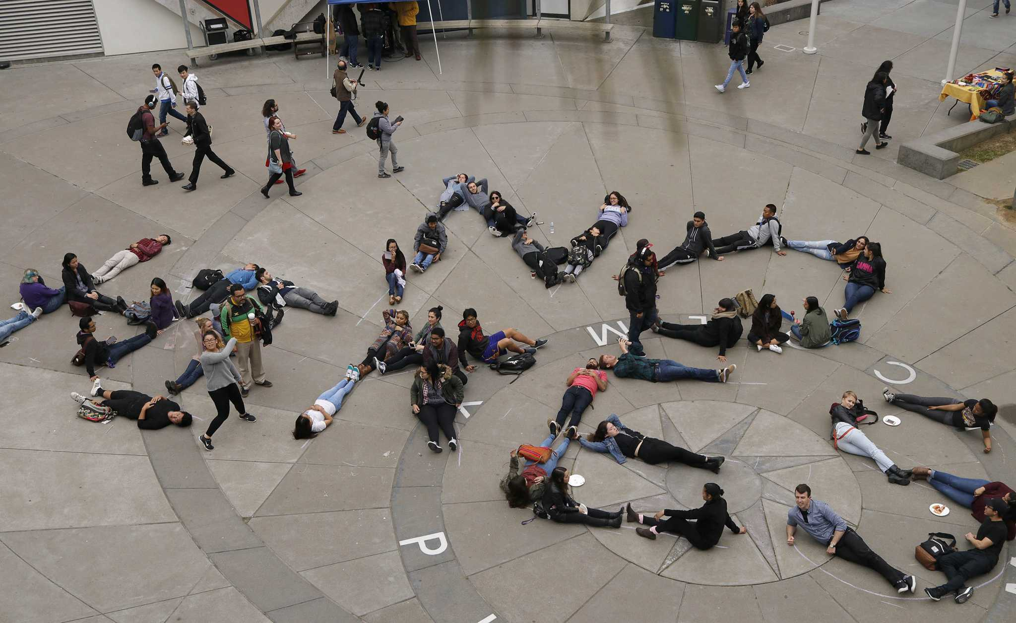"""Students spell out """"NO HIKES"""" with their bodies in the Malcom X Plaza in opposition of the tuition price hikes at SF State on Wednesday, March 15, 2017 in San Francisco Calif.. (Mason Rockfellow/Xpress)"""