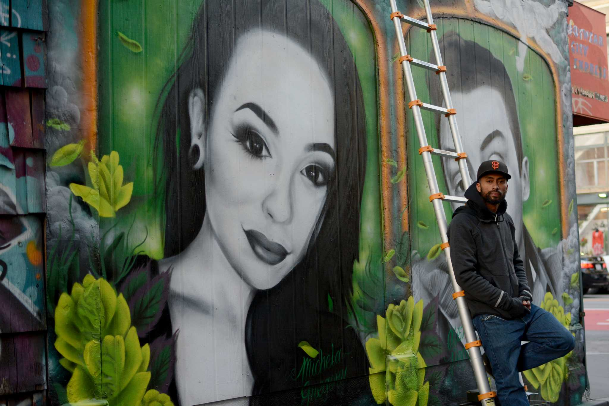 Mel Waters, 34, a muralist from San Francisco poses for a photograph to his mural of Michela Gregory, a former SF State student and her boyfriend Alex Vega on Friday, Feb. 24, 2017. ( Aaron Levy-Wolins/Xpress)