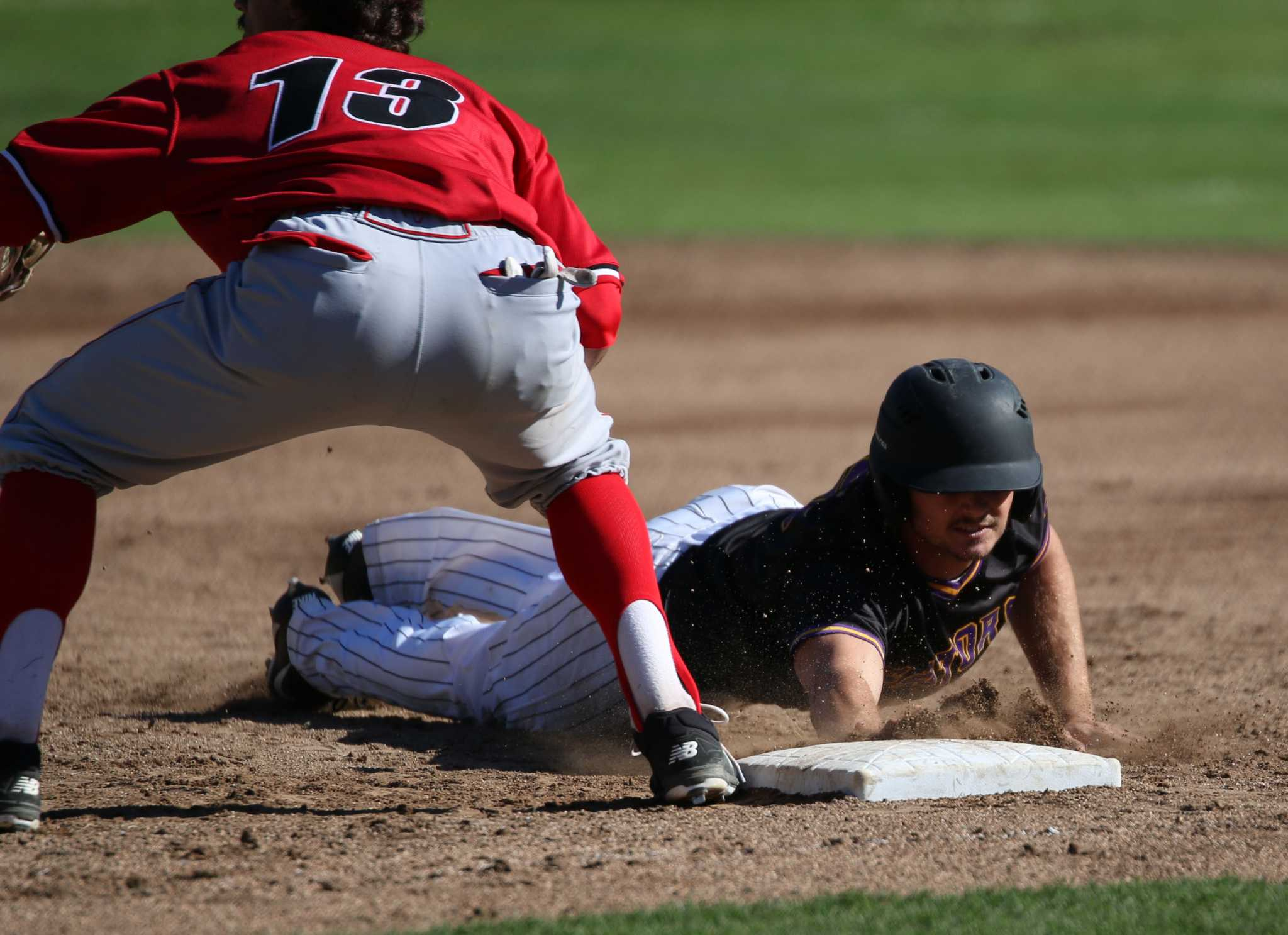 SF State junior outfielder, Zac Neumann (3), dives back to first base against Stanislaus State at SF State on March.11, 2017 (Kyler Knox/Xpress)
