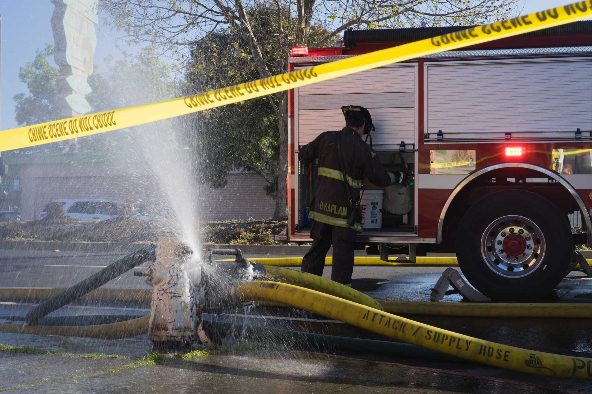 A firefighter works on the scene of an apartment fire in West Oakland on San Pablo and Mead Ave. on Monday, March 27, 2017 (Sarahbeth Maney/Xpress).
